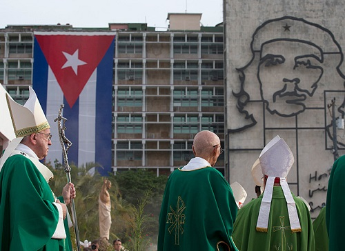 "Pope Francis holds his pastoral staff as he arrives to celebrate Mass at Revolution Plaza in Havana, Cuba, Sunday, Sept. 20, 2015, where a sculpture of revolutionary hero Ernesto ""Che"" Guevara and a Cuban flag decorate a nearby government building. Pope Francis opens his first full day in Cuba on Sunday with what normally would be the culminating highlight of a papal visit: Mass before hundreds of thousands of people in Havana's Revolution Plaza. (AP Photo/Alessandra Tarantino)"