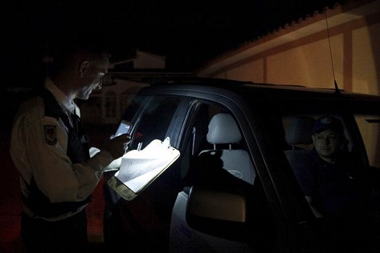 A watchman uses his phone's light at a condominium's checkpoint during a power cut in San Cristobal, in the state of Tachira, Venezuela, April 25, 2016. REUTERS/Carlos Eduardo Ramirez.