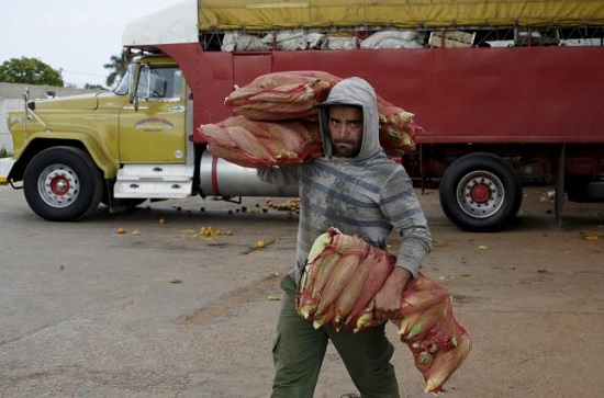 A man carries bags of maize at a wholesale market in Havana