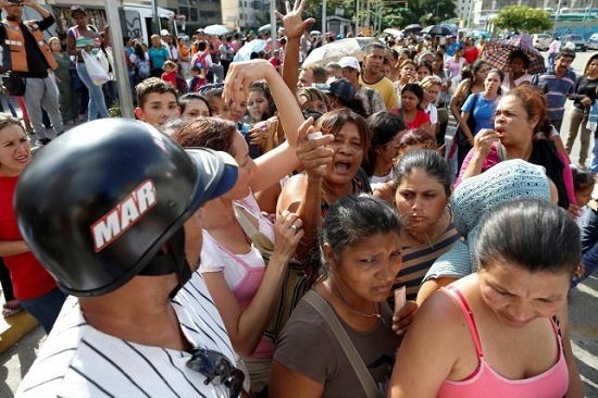 People shout while they queue to try to buy toilet paper and diapers outside a pharmacy in Caracas May 16, 2016. REUTERS/Carlos Garcia Rawlins