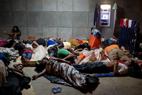 A Cuban woman migrant uses her cell phone while other Cubans sleep outside of the border control building in Penas Blancas, Costa Rica, on the border with Nicaragua, on Nov. 21, 2015. (AP Photo/Esteban Felix, File)